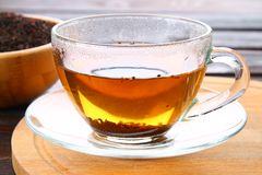 Hot black tea in a glass cup and dry tea on a wooden table. Hot black tea in a glass cup and dry tea on a wooden table Stock Photo