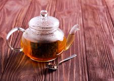 Hot black tea in glass tea pot, overhead on wooden table Stock Images