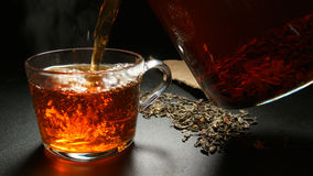 Hot black tea pouring to a cup from a teapot Stock Photography