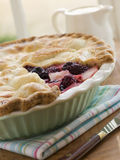 Hot Blackberry and Apple Pie. Resting on a tea towel with the top layer of crust taken off, to expose the fruits inside the pie Royalty Free Stock Photo