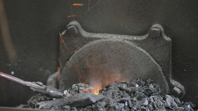 Hot blacksmith coals. Blacksmith stokes coals in a furnace to heat up a piece metal stock video footage