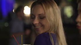 Hot blonde drinking cocktail, looking at sexy girl passionately, nightclub flirt. Stock footage stock video footage
