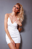 Hot Blonde girl. Beautiful fashion female model in white dress is posing on gray background Royalty Free Stock Photography