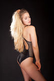 Hot blonde. Sexual blonde in body lingerie holding her hair Royalty Free Stock Image