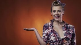 Commercial pattern with a cute blonde pin up model with amazing hairstyle and makeup. Hot blonde woman in vintage clothes in the pin up style, posing for a stock footage