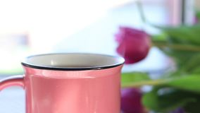 Hot boiling tea in pink ceramic cup with pairs on windowsill. Pink tulips near cup of tea stock footage