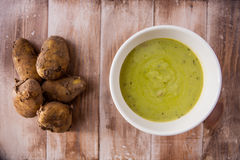 Hot bowl of pea soup with raw new potatoes Stock Photo