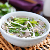Hot bowl of pho with beef and rice noodles. Shot close up with selective focus stock image