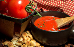 Hot Bowl Of Tomato Soup. Surrounded by fresh tomato with oyster crackers on a red and white gingham background Royalty Free Stock Images