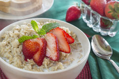 Hot breakfast. Hot bowl of oat meal with berries and toast royalty free stock photo