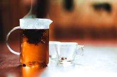 Hot brewed tea in transparent teapot and two cups on wooden background stock image