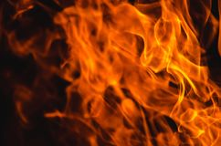 Hot bright burning flame on dark background. Hot bright orange burning flame on dark background. Abstract flamy backdrop with blurred and sharp areas Royalty Free Stock Photos