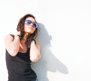 Hot brunette girl in hot sunlight. Hot summer sunlight on hot young brunette girl in front of white wall wearing sunglasses Stock Image