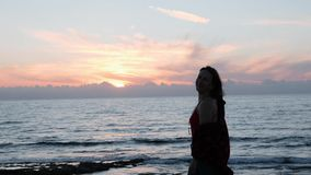Hot brunette girl posing for camera at sunset. Silhouette of young woman smiling and spinning around at rocky shore. Attractive gi stock video