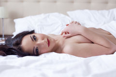 Hot brunette posing lying down looking at camera Royalty Free Stock Photos