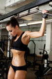Hot brunette pulls on crossbeam in gym Royalty Free Stock Photos