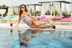 Hot brunette with sun glasses on pool side. Beautiful sexy brunette girl sitting on pool edge with fresh cocktail drink wearing swimsuit, sun glasses and hot Royalty Free Stock Photo