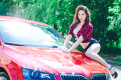 Hot brunette washes a red car on the road in summer Royalty Free Stock Photos