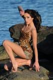 Hot brunette woman sitting on jetty Stock Photo