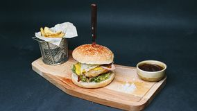 Hot burger with french fries and red sauce are on the board, pierced with a knife, and ready to eat in 4k resolution in stock video footage