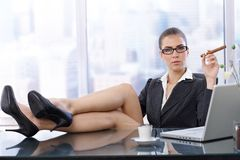 Hot businesswoman with feet on desk Stock Images