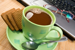 Hot cacao, biscuits  and computer. Stock Photo