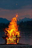 Hot camp fire of wood burning near water Stock Photos