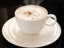 Hot cappuccino. A cup of hot cappuccino in white cup with saucer against black background stock photos