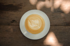 Hot Cappuccino art coffee. Cup of hot Cappuccino art coffee on wooden table Stock Photography