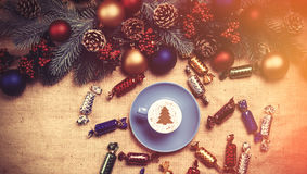 Hot cappuccino with christmas tree shape on a table near pine br Stock Photo