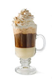 Hot Cappuccino Coffee. In a glass cup finished with whipped cream and cinnamon on white background Stock Image