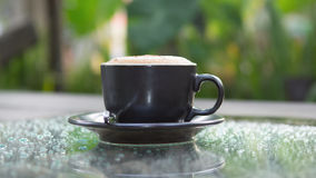Hot cappuccino coffee cup on grass table in garden with dewdrop Stock Photography