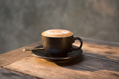 Hot cappuccino coffee cup on wooden table Royalty Free Stock Image
