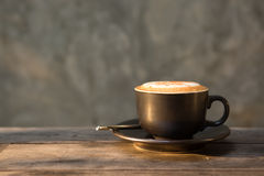 Hot cappuccino coffee cup on wooden table agent sunlight in morn Royalty Free Stock Photo