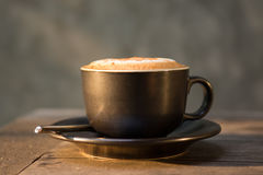 Hot cappuccino coffee cup on wooden table agent sunlight in morn Stock Photography