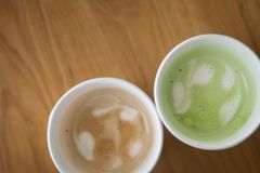 Hot Cappuccino coffee and hot green tea in paper cup. On a wooden table, top view Royalty Free Stock Photos