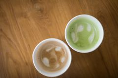 Hot Cappuccino coffee and hot green tea in paper cup. On a wooden table, top view Stock Photos