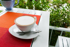 Hot cappuccino coffee in white ceramic cup on white wooden table Stock Photo