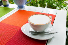 Hot cappuccino coffee in white ceramic cup on white wooden table Stock Photos