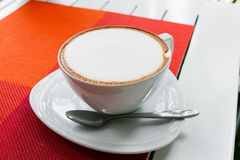 Hot cappuccino coffee in white ceramic cup on white wooden table Royalty Free Stock Photography