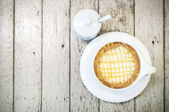 Hot cappuccino coffee in white cup on wodd background, vintage c Royalty Free Stock Photo