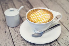 Hot cappuccino coffee in white cup on wodd background, vintage c Stock Photo