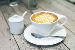 Hot cappuccino coffee in white cup on wodd background, vintage c Stock Images