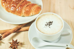 Hot cappuccino and croissant with cinnamon ,anise on wood table. In coffee shop Stock Photography