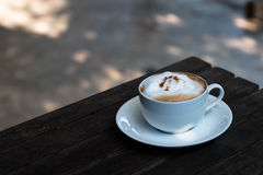 Hot Cappuccino in the cup on wood table Stock Image