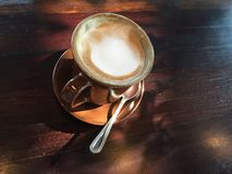Hot Cappuccino. A cup of hot cappuccino on wood table with morning light shadow from window Royalty Free Stock Images