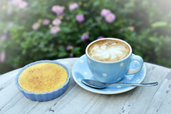 Hot cappuccino and custard with vintage garden background Stock Image
