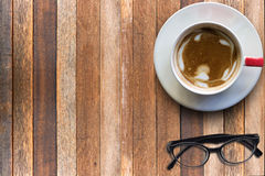 Hot cappuccino and eyeglasses on wooden Stock Photo