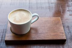 Hot Cappuccino with frothy milk foam. In white coffee cup on wooden table with copy space for text. Morning drink for refreshment Royalty Free Stock Image