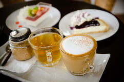 Hot cappuccino and hot tea with cakes. Royalty Free Stock Photos